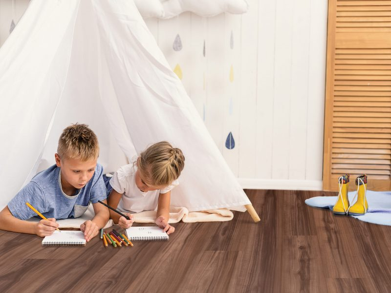 What are you drawing. Small cute brother and sister painting, using pencils while lying on floor in playroom